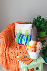 Skeins of wool lying in a white basket. Orange knitted blanket.