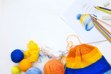 Knitting hat with stripes. Knitting. Balls and skeins.