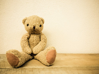 Brown teddy bear sit on the wooden floor.