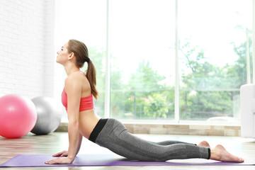 Dziewczyna ćwiczy postępowego joga na lekkim tle - 125441867