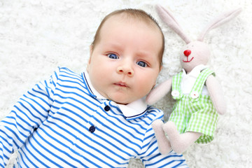 Cute baby with cuddly rabbit lying on white bedspread, close up view