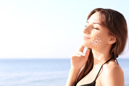 Young woman with sunscreen on face, sea background