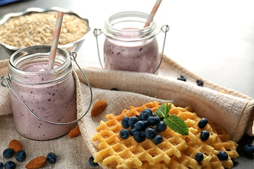 Two mason jars with tasty smoothie, wafers and some ingredients on blurred background