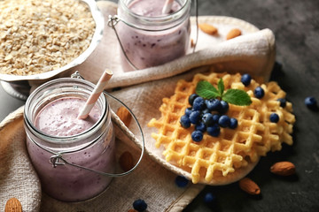 Mason jar with tasty smoothie, wafers and some ingredients on grey table