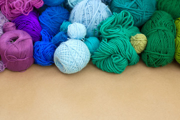 Colorful yarn stacked in a series of colors. Background brown.