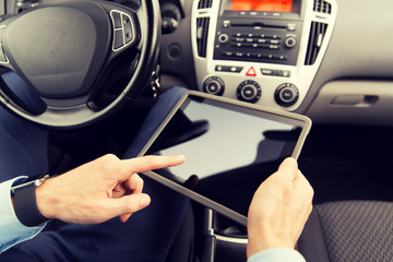 close up of young man with tablet pc driving car
