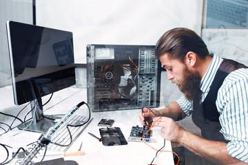 Repairman soldering circuit, double exposure. Bearded electrician welding electronic component of computer unit