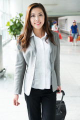 beautiful asian young girl with luggage is calling in airport