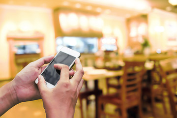Hand holding smartphone with abstract blur beautiful luxury restaurant interior for background concept. idea.