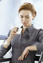 Unlucky businesswoman spilling coffee on blouse