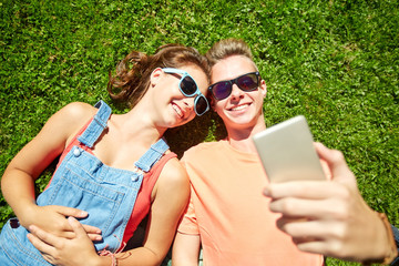 happy couple taking selfie on smartphone at summer