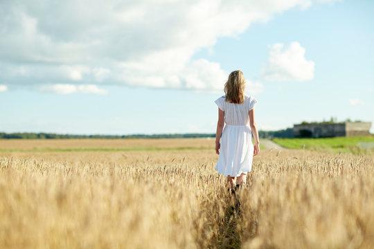 young woman in white dress walking along on field
