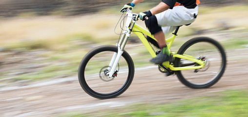 Cyclist riding a mountain bike downhill at high speed