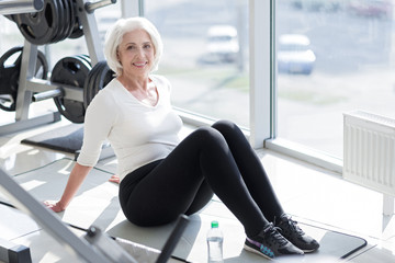 Cheerful senior woman relaxing in the gym.