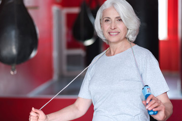 Smiling happy woman holding jumping rope