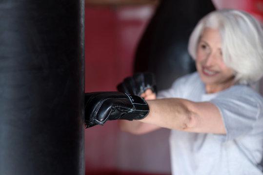 Motivated smiling senior woman boxing punching bag.