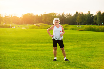 Senior woman with water bottle. Lady is standing on grass. Aerobic workouts improve health. All you need is motivation.