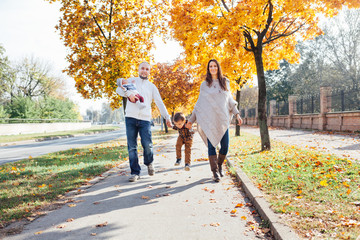 Happy family walking  in autumn city park