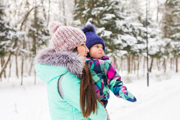Mother and little toddler girl walking in the winter forest and having fun with snow. Family enjoying winter. Christmas and lifestyle concept.