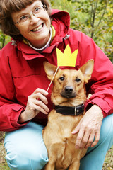 Old, smiling woman holding paper crown on stick close to dog's muzzle. Dog in funny, fake crown with ownerin park.