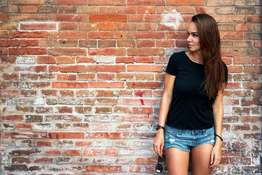 An outdoor portrait of a young pretty hipster girl with long dark hair wearing black blank t-shirt and blue jeans shorts standing on the brick wall background. Mock up.