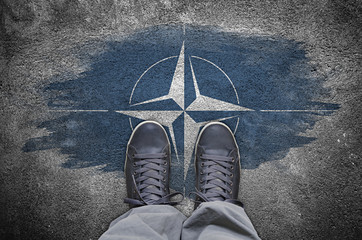 Sneakers standing on the grunge concrete floor with NATO flag