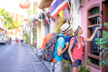 Travel and shopping. Young traveling couple with backpacks choose postcards in souvenir shop in Thailand.