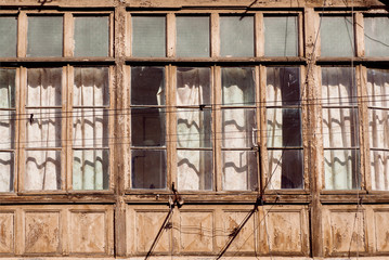 Poor rustic house with huge wooden windows frames in historical city