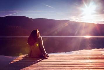 girl sitting on a bridge at the lake enjoying the sunshine