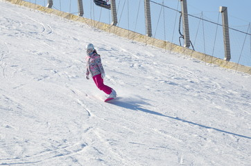 Girl on a snowboard down the mountain