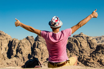 Self-satisfied man in hat on top mountain with thumbs up. Do not give up motivation concept. Happy hiker winning reaching life goal, success, freedom and achievement.