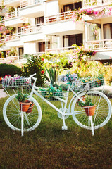 A decorative white bike with flower pots, nice hotel on the background. The white bicycle in the green garden