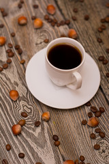 Small white cup of coffee, hazelnuts and cocoa beans on wooden background