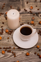 Small white cup of coffee, hazelnuts, cocoa beans, candle on wooden background