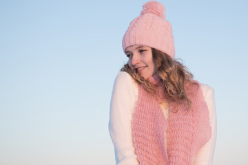Emotive portrait of a fashionable model in white standing at the winter field. Sunny weather. Outdoor shot.