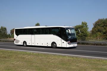Moderner Reisebus unterwegs auf gepflegtem Straßenabschnitt in Deutschland - Mit Ausstattung für alte Menschen und Behinderte!