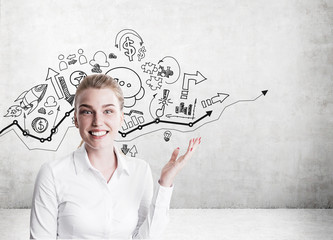 Blond woman showing startup sketches on concrete wall