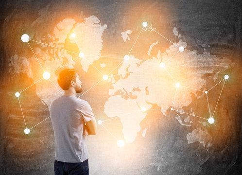 man in T-shirt standing near blackboard with world map