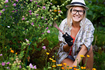 Young woman gardener sitting near flowers in garden holding hoe