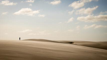 Solitary man walking through sand dunes, Lencois Maranhehses National Park, Brazil