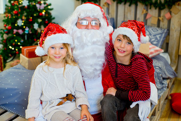 Fotobehang Carnaval Santa Claus and two children sitting on the bed