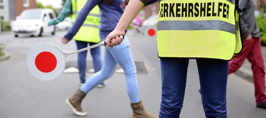 Schüler überqueren Übergang und Schülerlotse sichert Schulweg Ba