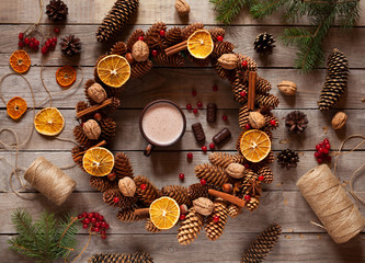 Christmas wreath of pine branches and cones, decorated with candied orange, nuts, cinnamon with hot cocoa on old vintage table.