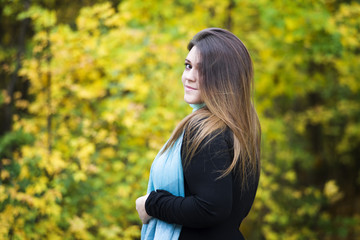 Young beautiful caucasian plus size model in black dress outdoors, xxl woman on nature, autumn atmosphere