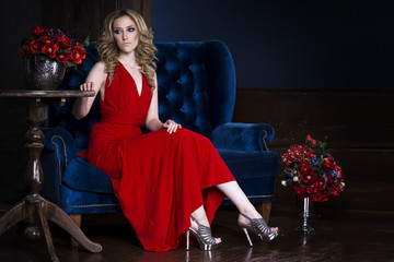 Young beautiful blonde caucasian woman with professional makeup and hairstyle in red dress posing in luxurious interior