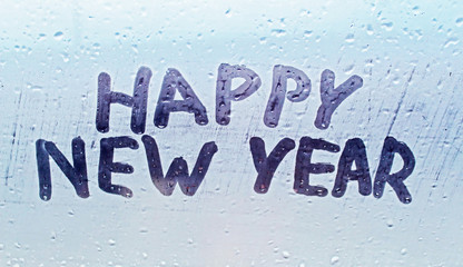 "The inscription ""happy new year"" on the misted window"