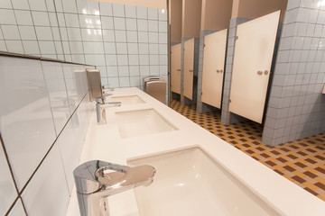 Several washbasin and seperated toilet cabins in huge bathroom of a hostel
