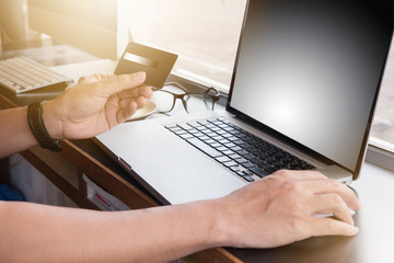 Cropped image of man inputting card information while shopping online