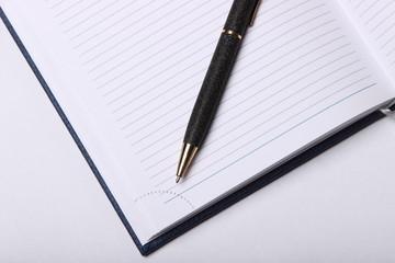 black ballpoint pen lying on a notebook
