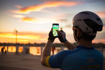 NONGKHAI, THAILAND - AUGUST 09 2016 : Male hand holding a  smartphone with a running Pokemon Go application at sunset. Fototapete